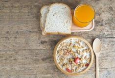 Bunken av frukostmysli med havren och vete flagar blandat med torkat - frukt och muttrar i en träbunke Royaltyfri Fotografi