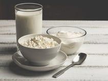 Bunken av vitkräm, ostmassa och hemlagat mjölkar på vit trälantlig bakgrund, sund mat för mejerilantgård Royaltyfri Fotografi