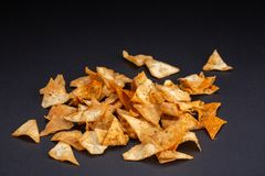 bunken chips potatisen En hög av chips som travas upp i en bunke Maten sitter på en svart bakgrund arkivfoton