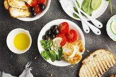 Bunken för osthaloumiråriers med tomater, oliv, citron och sörjer muttrar Top beskådar royaltyfria foton