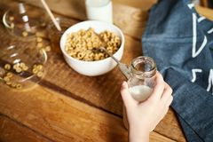 Bunken för ungehandinnehavet med den sunda frukosten med flingahonung mjölkar och honungskopan på tabellen fotografering för bildbyråer