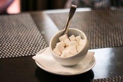 Bunken för vitt socker med stycken av socker och pincetten står på ett vitt tefat på en mörk tabell royaltyfri foto