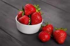 Bunken fyllde med nya mogna röda jordgubbar på trä Arkivbilder