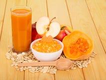Bunkepumpapuré, glass fruktsaft, äpplen på bakgrund tänder trä arkivfoton
