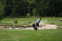 In the Bunker. Golf player trying to play out of the bunker stock image