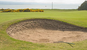 Bunker on golf course by the sea. An image of a bunker adjacent to a green of a golf course with a rake for players to smooth out any disturbances in the sand royalty free stock photos