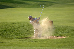 Bunker shot 3. A man blasts out of a bunker kicking up sand royalty free stock image