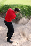 Bunker Shot. Young golfer hitting a shot out of a bunker Royalty Free Stock Photography