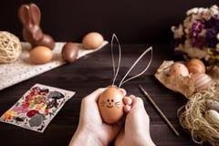 bunny Πάσχα Θηλυκά χέρια που κρατούν το αυγό Πάσχας στον ξύλινο πίνακα Στοκ Εικόνες