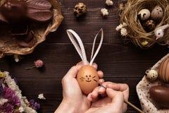 bunny Πάσχα Θηλυκά χέρια που χρωματίζουν το αυγό Πάσχας στον ξύλινο πίνακα Στοκ Φωτογραφία