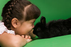 Bunny. Girl and rabbit have nestled to each other noses Royalty Free Stock Photos