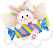 Bunny angel with candy on the cloud Stock Photo