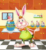 A bunny baking an egg-designed cupcakes. Illustration of a bunny baking an egg-designed cupcakes Stock Photo