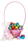 A Bunny and a Basket with Chocolate Easter Eggs. A Toy Bunny and Colorful Basket full of Chocolate Easter Eggs Royalty Free Stock Photo
