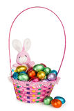 A Bunny and a Basket with Chocolate Easter Eggs. A Toy Bunny and Colorful Basket full of Chocolate Easter Eggs Stock Photos