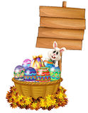 A bunny and a basket with eggs near a signage Royalty Free Stock Photo
