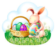 A bunny and a basket full of easter eggs Royalty Free Stock Image