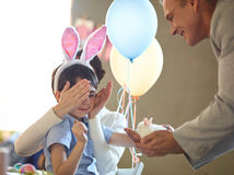 Bunny for birthday. Little son looking at his birthday gift in father hands royalty free stock photo