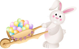 Bunny carrying wheel barrow full with carrots Easter eggs Royalty Free Stock Photos