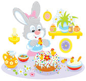 Bunny cooks a holiday cake. Easter rabbit decorating a fancy cake for the holiday table Stock Images
