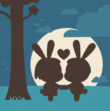 Bunny Couple Kissing Under Tree. Vector illustration of a cartoon bunny couple kissing and holding hands under a tree and the moonlight Stock Photo