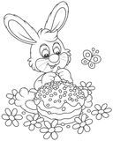 Bunny with an Easter cake. Easter rabbit with a decorated holiday pie among flowers, a black and white vector illustration in a cartoon style for a coloring book Stock Photos