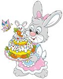 Bunny with an Easter cake. Easter rabbit holding a freshly backed and colorfully decorated holiday cake Royalty Free Stock Image