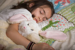 Bunny and girl sleeping. Girl sleeping with bunny gift on the Easter holidays Stock Photo
