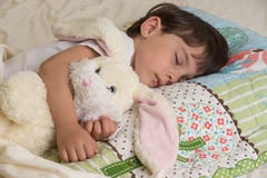 Bunny and girl sleeping. Girl sleeping with bunny gift on the Easter holidays Stock Photography