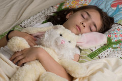 Bunny and girl sleeping. Girl sleeping with bunny gift on the Easter holidays Royalty Free Stock Images