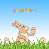 Bunny in grass. Easter background. Cute bunny with easter eggs sitting in green grass Royalty Free Stock Image