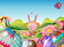 A bunny with a guitar and the easter eggs in the garden Royalty Free Stock Photo