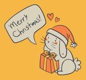 Bunny Holding dibujado mano un presente y desear una Feliz Navidad Foto de archivo