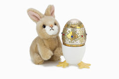 Bunny and Jeweled Egg. This is an image isolated on a white background of a cute little stuffed rabbit with a beautiful hand decorated jeweled egg Royalty Free Stock Photos
