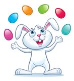 Bunny Juggling Easter Eggs. Cartoons of a cute bunny that is juggling colorful Easter eggs in the air Stock Image