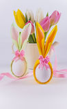 Bunny napkin eggs for easter and flowers on white background. Easter eggs wrapped as bunnies and tulips on white background Royalty Free Stock Images