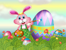 A bunny painting the egg in the garden Royalty Free Stock Photography