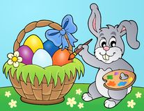 Bunny painting eggs in basket Stock Images