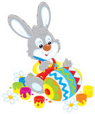 Bunny paints an Easter egg. Little rabbit coloring a big Easter egg to the holiday Stock Images