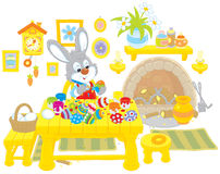 Bunny paints Easter eggs. Little rabbit coloring Easter eggs to the holiday Stock Images