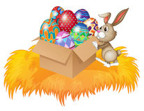 A bunny pushing a box full of easter eggs Stock Photos