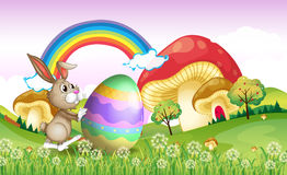 A bunny pushing an easter egg Stock Images
