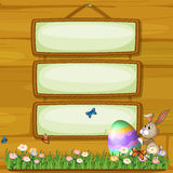 A bunny pushing an egg in front of the hanging signage Stock Images