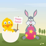 Bunny Rabbit & Chick with Easter Egg. A Happy Easter greeting card with a cute bunny rabbit holding a Easter egg and a chick into an eggshell in a meadow Stock Photo