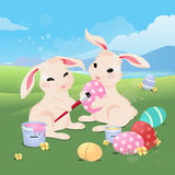 Bunny rabbit painting easter eggs. In grass field under blue sky Stock Image