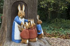 Bunny Rabbit Sculptures. Peter Rabbit scene, Mother and kids bunny rabbit sculptures made of wood beside a tree stock photography