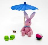 Bunny rabbit teddy on beach. Bunny rabbit teddy beach under parasol with items associated with beach, white background Royalty Free Stock Photo