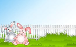 Bunny Rabbits Sitting In Grass. An illustration featuring a pair of bunny rabbits sitting in grass with white picket fence and blue sky Stock Photo