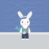 Bunny sailor holds in paws fish Royalty Free Stock Photo