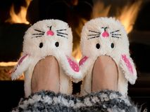 Bunny slippers by fireplace. Pair of bunny slippers by home fireplace with striped handmade afghan royalty free stock photo